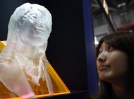 A woman looks at a rapid prototyping model of her face made by a 3 D printer