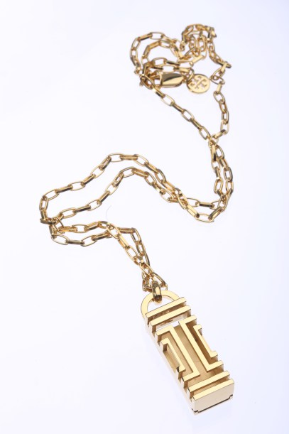A Fit Bit necklace in gold from Tory Burch.