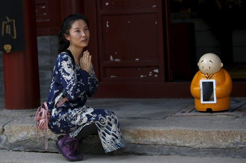 A visitor asks a temple staff to give her chance to take picture with robot Xian'er which is placed in the main building of Longquan Buddhist temple for photograph, on the outskirts of Beijing, April 20, 2016.  REUTERS/Kim Kyung-Hoon
