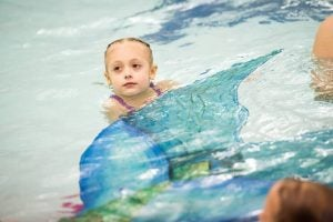 Kids swim with mermaids