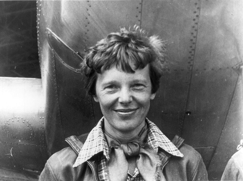 Amelia Earhart standing under nose of her Lockheed Model 10 E Electra small