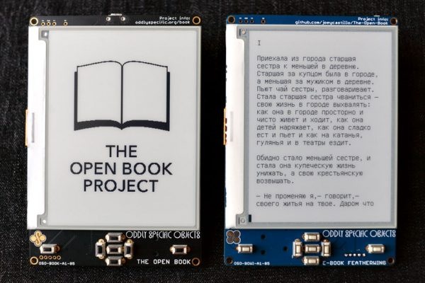 Close-up photo of two devices; at left the Open Book displays the project's name; at right, the E-Book Feather Wing displays a page of text in Russian.
